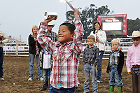 """Joaquin Olivarria, 7, of Soledad holds his winning """"mutton-bustin"""" trophy aloft at the opening ceremonies for the 2013 California Rodeo Salinas on Thursday night."""