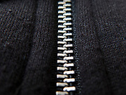 Close up of a zipper. A zipper, zip, fly or zip fastener, formerly known as a clasp locker, is a commonly used device for binding the edges of an opening of fabric or other flexible material, as on a garment or a bag.