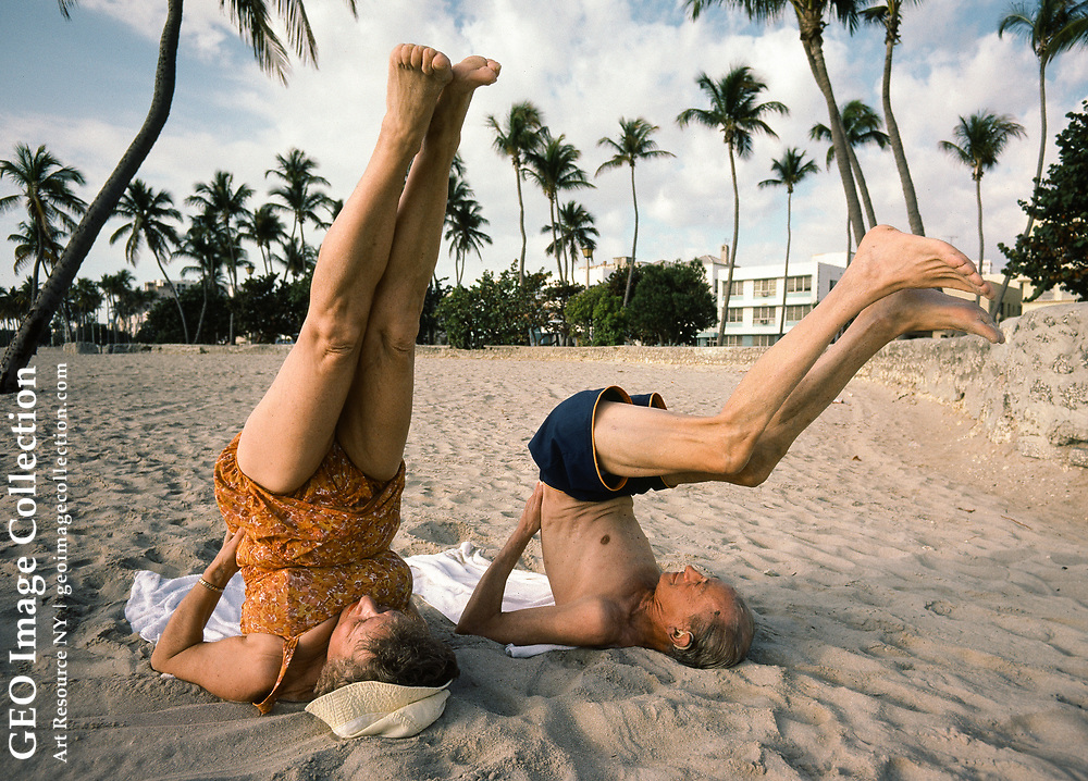 Elderly man and woman doing outdoor early morning yoga exercises in sand on beach at Miami Beach, Florida. The yoga helps keep Eli and Helen Fricklas healthy and limber, even as a geriatric old couple.