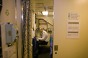 A Weapons Engineering Officer works in his cabin quarters aboard HMS Vigilant, a Vanguard class nuclear submarine.
