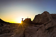 Sunset Illuminates a Silhouette of a Woman on a Boulder in Paria Rocks on the Colorado Plateau Arizona
