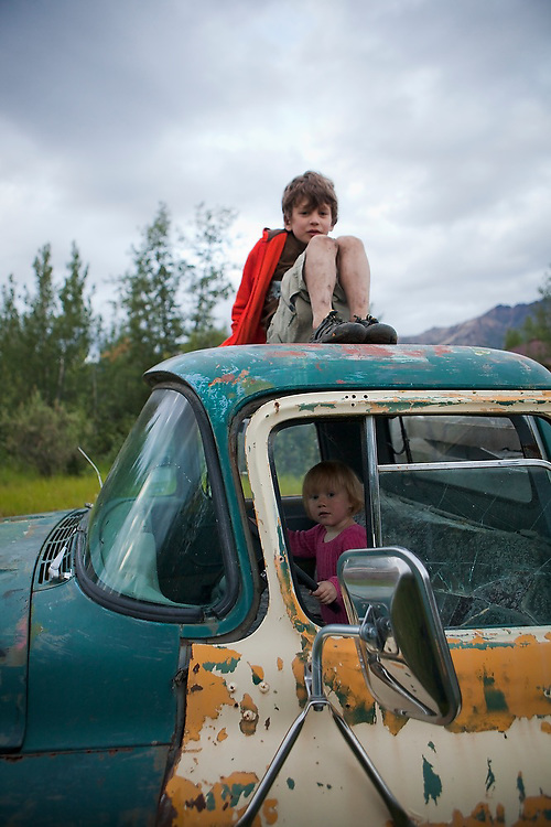 Young children play in and on one of the many old abandoned trucks scattered around the town of McCarthy, Alaska.