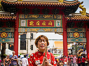 """19 FEBRUARY 2015 - BANGKOK, THAILAND: A woman prays at the entrance to the Thian Fah Shrine in Bangkok's Chinatown. 2015 is the Year of Goat in the Chinese zodiac. The Goat is the eighth sign in Chinese astrology and """"8"""" is considered to be a lucky number. It symbolizes wisdom, fortune and prosperity. Ethnic Chinese make up nearly 15% of the Thai population. Chinese New Year (also called Tet or Lunar New Year) is widely celebrated in Thailand, especially in urban areas that have large Chinese populations.    PHOTO BY JACK KURTZ"""