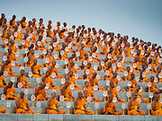 """22 FEBRUARY 2016 - KHLONG LUANG, PATHUM THANI, THAILAND:  Buddhist monks sit around the chedi during Makha Bucha Day at Wat Phra Dhammakaya.  Makha Bucha Day is a public holiday in Cambodia, Laos, Myanmar and Thailand. Many people go to the temple to perform merit-making activities on Makha Bucha Day, which marks four important events in Buddhism: 1,250 disciples came to see the Buddha without being summoned, all of them were Arhantas, Enlightened Ones, and all were ordained by the Buddha himself. The Buddha gave those Arhantas the principles of Buddhism, called """"The ovadhapatimokha"""". Those principles are:  1) To cease from all evil, 2) To do what is good, 3) To cleanse one's mind. The Buddha delivered an important sermon on that day which laid down the principles of the Buddhist teachings. In Thailand, this teaching has been dubbed the """"Heart of Buddhism."""" Wat Phra Dhammakaya is the center of the Dhammakaya Movement, a Buddhist sect founded in the 1970s and led by Phra Dhammachayo.     PHOTO BY JACK KURTZ"""