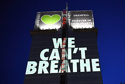 """© Licensed to London News Pictures. 05/07/2020. London, UK.  A light projection reading'WE CAN'T BREATHE'is cast onto the shell of Grenfell Tower in West Londonon the eve of the second phase of the Grenfell Tower Fire Inquiry. The slogan echoes the words spoken on the night recorded oncalls to emergency services and loved onesbegging for help that never came.<br /> Abbas Dadou, Chairman of Lancaster West Estate Residents Association comprising 800 homes and 2000 residents said """"We stand in solidarity with the families who lost their loved ones in their fight for justice. They are us and we are with them. They are part of our community and their fight for justice is our fight."""" El Alami Hamdan who lost his daughter and his grandchildren in the fire said """"how long must we wait for justice? It has been three years and still nothing. They promise everything and they do nothing.'<br /> <br /> A press conference will be held this morning ahead of the Inquiry resuming, where the followingstatement will be released at 10am:<br /> 'Family members of those who perished in the fire that took the lives of 72 people on June 2017 were present last night when the projection of 'We can't breathe' was cast on the now iconic building """"These words echo what we heard on the 999 calls of our loved ones, or the last final breath taken by our brothers and sisters, mothers and fathers and our children that night as they begged for help. We have had to listen to these calls as part of the Inquiry going through the pain of their suffering and the complete failures which cost our loved ones' tragic deaths that night. We are no longer going to keep silent. We demand justice. We want prosecutions. We are not willing to wait as these words echo in our heads everyday. It is heartbreaking but this projection is also a powerful message from us to the authorities that we will be heard. When we think of what family members went through that night, all we hear is 'we can't breathe. All we imagine is"""