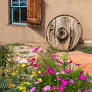 Summer wildflowers make a colorful foreground for this rustic Southwest window in Taos, New Mexico