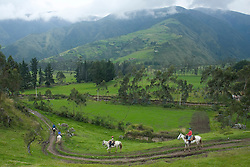tourists riding horses through fields below mountains with cloudforest,Zuleta, Ecuador, South America.  MR
