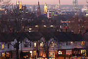Early evening lights glow from windows of Edwardian era semi-detached houses with 100 year-old mature ash trees Westminster and city behind, SE24