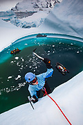 Woman climber ice climbing on grounded iceberg, Cruise ship passengers look on, Pleneau Island, Antarctic Peninsula