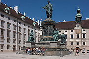 Young women sit beneath the monument to Emperor Franz 2nd in the courtyard of the Hofburg Kaiserappartements, on 28th June 2016 in Vienna, Austria. Hofburg Palace is the former imperial palace forming part of the official residence and workplace of the President of Austria. Built in the 13th century and expanded in the centuries since, the palace has housed some of the most powerful people in European and Austrian history, including monarchs of the Habsburg dynasty, rulers of the Austro-Hungarian Empire.