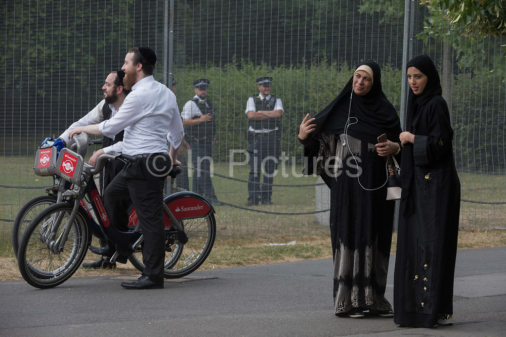 Jewish men, Muslim ladies with UK Met police officers who guard a temporary perimeter fence encircling Winfield House, the official residence of the US Ambassador during the visit to the UK of US President, Donald Trump, on 12th July 2018, in Regents Park, London, England.