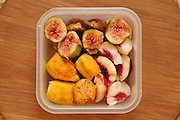 Fresh peeled and cut fruit in a lunch box containing peaches, figs and prickly pear