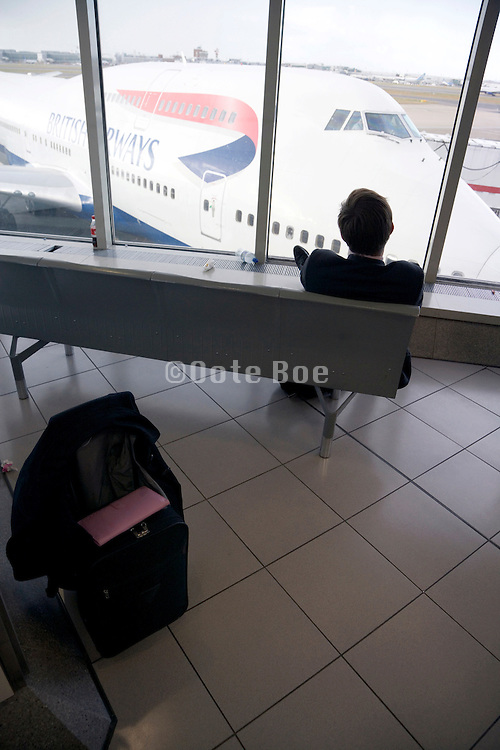 businessman staring out of the window to his delayed airplane