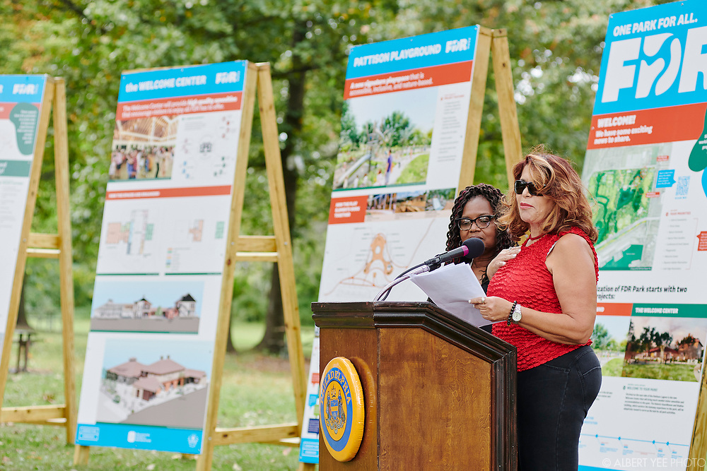 Barbara Capozzi [red short sleeve top and sunglasses], Friends of FDR Park and Karen Harris [black jacket and glasses], Friends of FDR Park<br /> Fairmount Park Conservancy, the City of Philadelphia, elected officials, and the Friends of FDR Park will reveal new designs for FDR Park, soliciting community input on future usage, and announce significant city investment in this South Philadelphia treasure. Program will highlight the coming play space and Welcome Center at FDR Park with a speaking program and unveiling.<br /> <br /> DETAILS: Fairmount Park Conservancy, the non-profit organization that brings Philadelphia parks to life, in partnership with Philadelphia Parks & Recreation and the Friends of FDR Park, recently began the implementation of the FDR Park Master Plan, a vision that offers a once-in-a generation opportunity to reimagine a historic Olmsted Park to serve 21st-century Philadelphians.<br /> <br /> The Gateway Phase of the master plan will enhance the visitor experience by restoring and transforming the 5,500 square foot guardhouse at FDR Park's Broad Street and Pattison Avenue entrance into a Welcome Center. The Welcome Center will include a courtyard with restrooms, a staffed information center, equipment rentals, food vendors, and co-working spaces for park staff and community partners. The Welcome Center will also transform the existing stables into a 4,000-square- foot cafe and 6,700-square-foot event space overlooking the Pattison Lagoon.<br /> <br /> Adjacent to the Welcome Center will be a world-class destination play space that encourages nature play. Park-goers of all ages and abilities will be able to enjoy the playscape with rolling paths, climbing structures, log scrambles, and treehouses. A mega-swing set will provide a unique swing experience unlike any other in the city, overlooking the Pattison Lagoon.<br /> <br /> Learn more about the FDR Park Master Plan: https://myphillypark.org/what-we-do/capital-projects/fdr-park/<br /> <br /> f