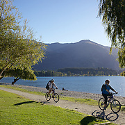Cyclists cycle around a Lake Wanaka cycle track. Wanaka is  a year round destination set against the pristine alpine backdrop of Mount Aspiring National Park in Central Otago. South Island, New Zealand. 1st April 2011. Photo Tim Clayton.