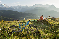 Mountain biker relaxing on alpine landscape and looking at map, Bavaria, Germany