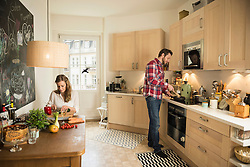 Couple in kitchen and preparing food, Munich, Bavaria, Germany