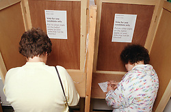 Two women with learning difficulties voting in polling booths,