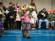 11 DECEMBER 2019 - DES MOINES, IOWA: A woman carries flowers for an offering into the gym at Our Ladies of the Americas Church during the Virgin of Guadalupe celebration at the church in Des Moines. Virgin of Guadalupe Day is one of the most important holy days in Mexican Catholicism. It marks Dec. 12, 1531, the day Juan Diego, an indigenous Mexican peasant, saw an apparition of the Virgin Mary on a barren hillside in what is now Mexico City. A basilica was built on the site. Virgin of Guadalupe Day is celebrated throughout Mexico and in Mexican communities in the United States.              PHOTO BY JACK KURTZ
