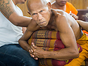"07 MARCH 2015 - NAKHON CHAI SI, NAKHON PATHOM, THAILAND: A Buddhist monk gets a Sak Yant tattoo during the Wat Bang Phra tattoo festival. Wat Bang Phra is the best known ""Sak Yant"" tattoo temple in Thailand. It's located in Nakhon Pathom province, about 40 miles from Bangkok. The tattoos are given with hollow stainless steel needles and are thought to possess magical powers of protection. The tattoos, which are given by Buddhist monks, are popular with soldiers, policeman and gangsters, people who generally live in harm's way. The tattoo must be activated to remain powerful and the annual Wai Khru Ceremony (tattoo festival) at the temple draws thousands of devotees who come to the temple to activate or renew the tattoos. People go into trance like states and then assume the personality of their tattoo, so people with tiger tattoos assume the personality of a tiger, people with monkey tattoos take on the personality of a monkey and so on. In recent years the tattoo festival has become popular with tourists who make the trip to Nakorn Pathom province to see a side of ""exotic"" Thailand.   PHOTO BY JACK KURTZ"