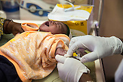 A nurse inserts a cannula into 3 day old baby Brighton who has a fever, carefully watched by Francisca Peter the mother on the infrared baby warming machine on the NICU (Neonatal Intensive Care Unit) Ward. St Walburg's Hospital, Nyangao. Lindi Region, Tanzania.