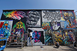 "© Licensed to London News Pictures. 28/05/2018. LONDON, UK. Street artists (L to R) Jim Vision, Core246 and Samer at work at ""Meeting of Styles"" near Brick Lane in East London.  The three day festival celebrates street art, with artists from around the world demonstrating their skills.  Photo credit: Stephen Chung/LNP"