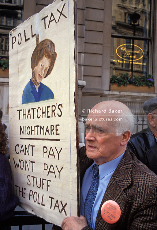 Before it erupts into a full-scale riot, peaceful protesters against Margaret Thatcher's Poll Tax policy, gather in Whitehall, on 31st March 1990, in London, England. London, England. Later that day, angry crowds stormed the Whitehall area and then London's West End, setting fire to a construction site and cars, looting stores up Charing Cross Road and St Martin's Lane. The anti-poll tax rally in central London erupted into the worst riots seen in the city for a century. Forty-five police officers were among the 113 people injured as well as 20 police horses. 340 people were arrested.
