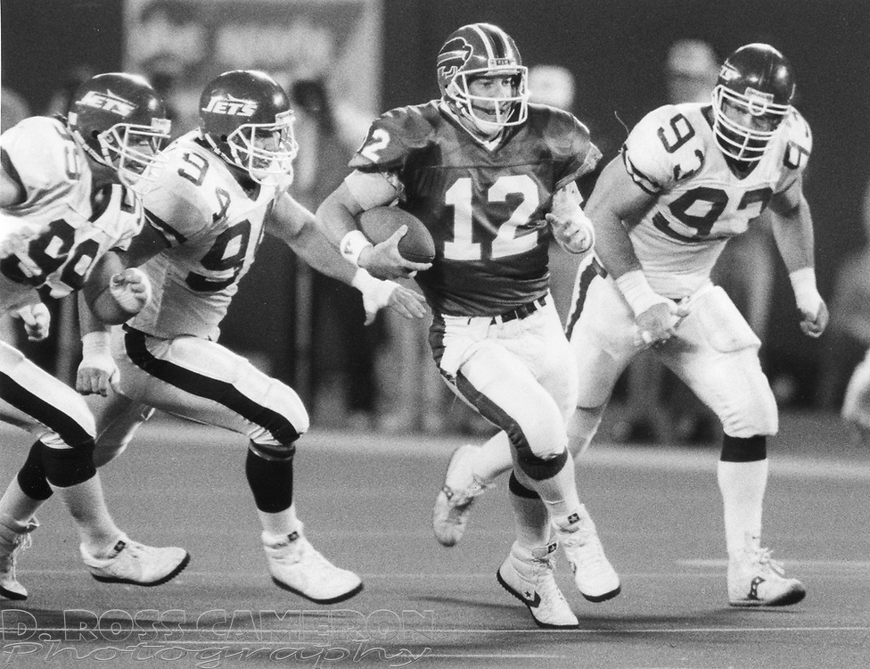 Buffalo Bills quarterback Jim Kelly (12) scrambles away from New York Jets defensive linemen Mark Gastineua (99), Scott Mersereau (94) and Marty Lyons during the second quarter of an NFL football game, Monday, Oct. 17, 1988 at Giants Stadium in East Rutherford, N.J. The Bills won, 34-17. (D. Ross Cameron/The Express)