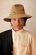 A Tibetan man wearing nice clothes poses for a photograph in Yushu, Tibet.