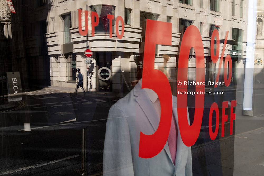 The window of a menswear outfitters displays a 50% reduction on some stock during the Coronavirus pandemic in the City of London, the capital's financial district, on 30th July 2020, in London, England.