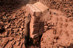 November 21, 2018 - Dhaka, Bangladesh - A man stacks more than a dozen bricks on his head while working at a brickfield in Dhaka, Bangladesh. (Credit Image: © Kazi Salahuddin Razu/NurPhoto via ZUMA Press)