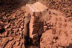 November 21, 2018 - Dhaka, Bangladesh - A man stacks more than a dozen bricks on his head while working at a brickfield in Dhaka, Bangladesh. (Credit Image: © Kazi Salahuddin Razu/NurPhoto via ZUMA Press)