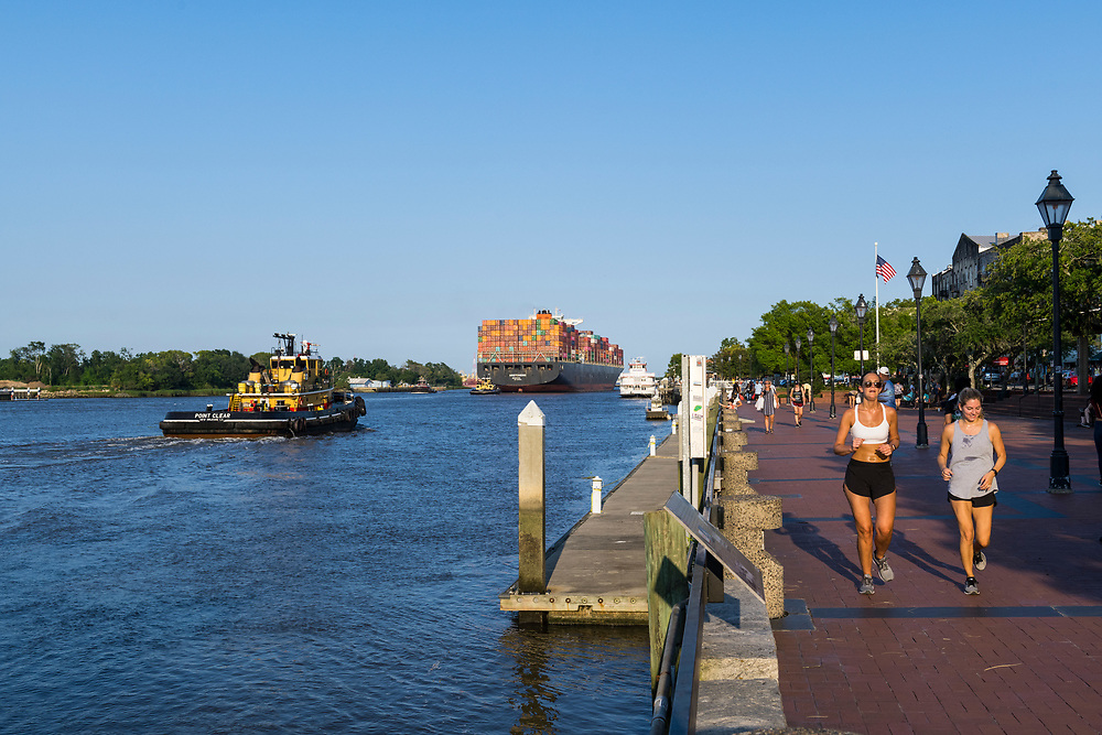 Savannah, Georgia, USA - July 29, 2021: Late on a summer afternoon, two women jog on the riverfront as a container ship called Aristomenis departs the deep water port of Savannah.