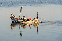 Mozambican freshwater fishers polling their boat on an open lake, Panda, Inhambane Province, Mozambique