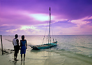 Couple enjoy the view at sunset over the Gulf of Mexico on Isla de Holbox, Mexico.