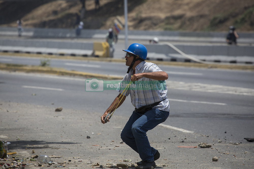 May 1, 2019 - Caracas, Venezuela - An anti-government protester runs during clashes with security forces in the surroundings of La Carlota military base in Caracas during the commemoration of May Day on May 1, 2019 after a day of violent clashes on the streets of the capital spurred by Venezuela's opposition leader Juan Guaido's call on the military to rise up against President Nicolas Maduro. Guaido called for a massive May Day protest to increase the pressure on President Maduro. (Credit Image: © Jonathan Lanza/NurPhoto via ZUMA Press)