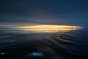 Sunset with reflections in the waves, north of Spitzbergen, slightly panned | Solnedgang med refleksjon i bølgene, nord for Svalbarg. Panorert.