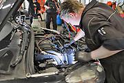 Nederland, Malden, 16-6-2017Een automonteur in een garage die gespecialiseerd is in Peugeot en Citroen vervangt een deel van de airco.Foto: Flip Franssen