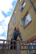 An Orthodox Jewish boy climbing on a fence in front of a block of flats with open windows in Reizel close an Agudas Israel Housing Association development for low-income Orthodox Jewish families in Stamford Hill, London.