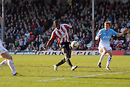 Brentford's Clayton Donaldson has a shot at goal . Skybet football league one match , Brentford v Bradford City at Griffin Park in Brentford, London  on Saturday 8th March 2014.<br /> pic by John Fletcher, Andrew Orchard sports photography.