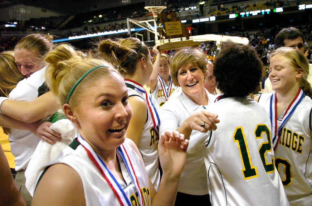 Rock Bridge players (left to right) Katherine Harry, Lauren Kelly, Rachel Rutter, Kelsie Shearrer, Amaya Williams, and Andrea Seabaugh, share the excitement of their win with Rock Bridge principal Kathy Ritter, center, after their 50-35 state championship win over Incarnate Word.
