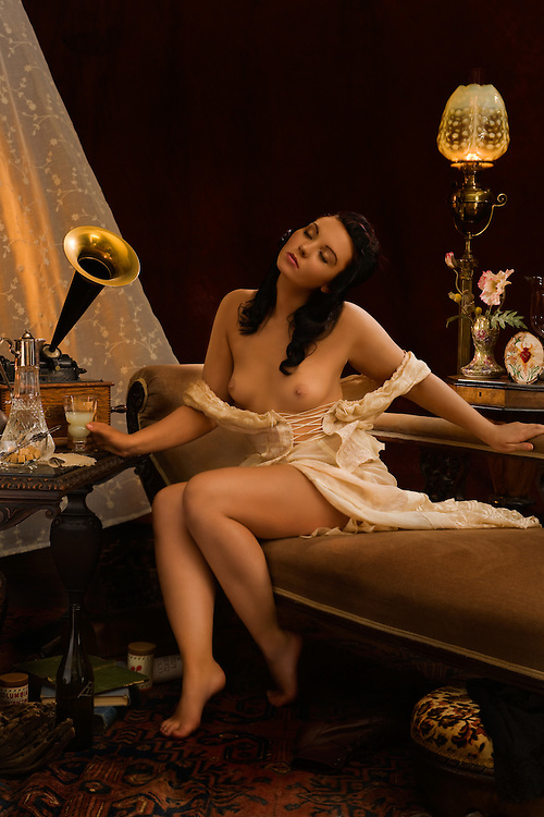 Scene set in Paris circa Paris 1910. A beautiful young woman listens to music while enjoying a glass of absinthe. Model - Sabrina Sin. Scene set in Paris circa Paris 1910. A beautiful young woman listens to music while enjoying a glass of absinthe. Model - Sabrina Sin