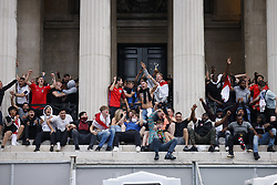 © Licensed to London News Pictures. 11/07/2021. London, UK. England supporters perched on the entrance to The National Gallery in central London react to the EURO 2020 final between Italy and England as they watch the giant screens in Tragalgar Square. Photo credit: Peter Macdiarmid/LNP
