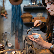 Rosa Kilgore files and hammers precious metals in her Scottsdale studio. The jewelry designer is the daughter of two artists.<br /> <br /> _____________________________<br /> <br /> One family, three artists.<br /> <br /> Nicholas Bernard, potter; Linda Margaret Kilgore, mixed media artist; and Rosa Kilgore, Linda's daughter, jeweler.<br /> The three of them have a strong interest in archeology and cultural anthropology, which drew each of them strongly to their own artistic expression.<br /> <br /> Linda's mom and Rosa's grandmother had businesses on the Navajo/Hopi Reservation and was an American Indian art dealer for many years. Both of them grew up steeped in those cultures.<br /> <br /> Nick's mother is an archeologist, and his love of the ancient has inspired his work.