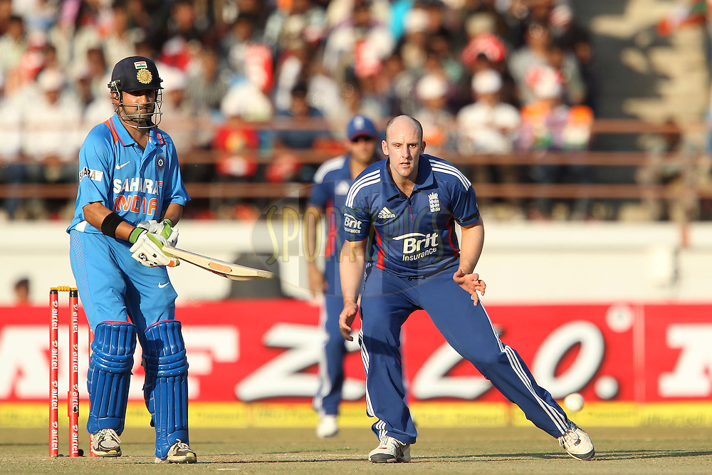 James Tredwell of England fields as Gautam Gambhir of India looks on during the 1st Airtel ODI Match between India and England held at the SAURASHTRA CRICKET ASSOCIATION STADIUM, RAJKOT, India on the 11th January 2013..Photo by Ron Gaunt/BCCI/SPORTZPICS ..Use of this image is subject to the terms and conditions as outlined by the BCCI. These terms can be found by following this link:..http://www.sportzpics.co.za/image/I0000SoRagM2cIEc