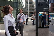 A missing panel in a street directions sign, frames a businessman on his phone admiring a young woman who looks up at the Monument where the Great Fire of London of 1666 is commemorated exactly 350 years afterwards, on 1st September 2016, in the City of London, England UK.