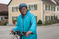 Happy senior man with cycling helmet on his bicycle, Bavaria, Germany
