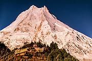 Buddhist monastery in village of Lho with Manaslu 8169 m towering above, Manaslu Himalaya, Nepal