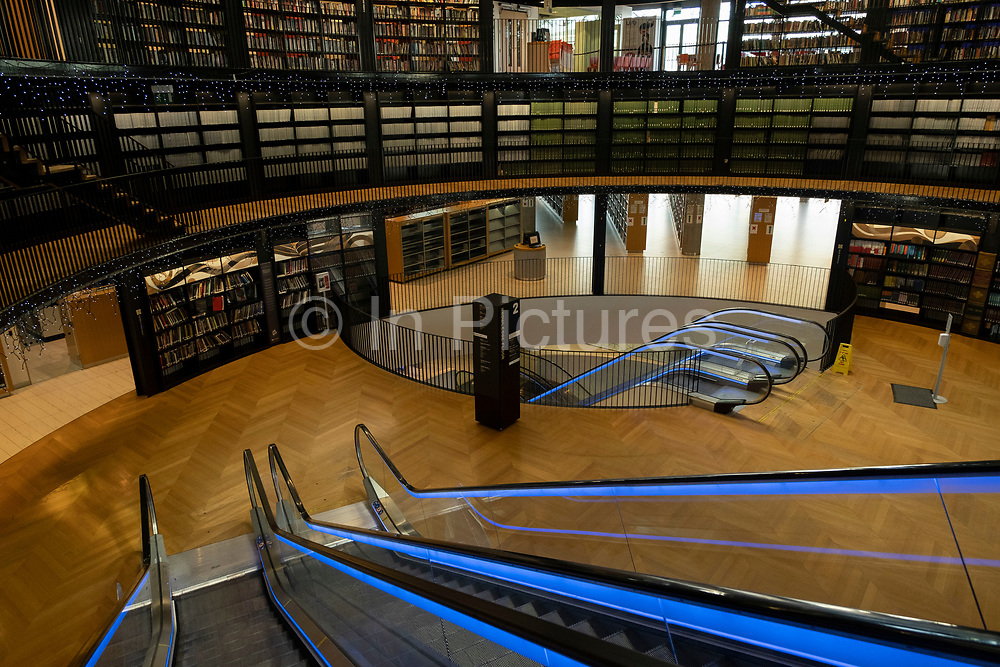 Interior of escalators and architectural detail in the Library of Birmingham on 15th June 2021 in Birmingham, United Kingdom. The Library of Birmingham is a public library in Birmingham, England. It is situated on the west side of the city centre at Centenary Square, beside the Birmingham Rep to which it connects, and with which it shares some facilities and Baskerville House. Upon opening on 3 September 2013, it replaced Birmingham Central Library. The library is viewed by the Birmingham City Council as a flagship project for the citys redevelopment. It has been described as the largest public library in the United Kingdom, the largest public cultural space in Europe, and the largest regional library in Europe.