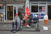 Tired sikh gentlemen rest outside an ice cream parlour on the Eastern Esplanade at Southend-on-Sea, Essex.